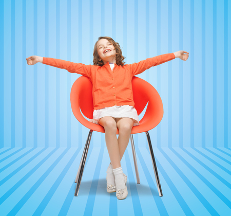 spreaded: people, happiness, childhood and furniture concept - happy little girl sitting on chair with spreaded arms over blue striped background