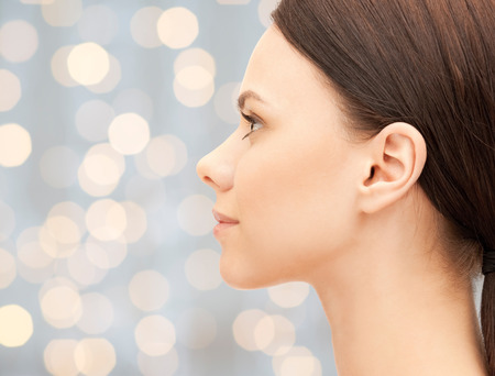 health, people and beauty concept - beautiful young woman face over holidays lights background Stock Photo