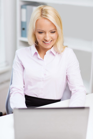 social networking: education, business and technology concept - smiling businesswoman or student with laptop computer in office