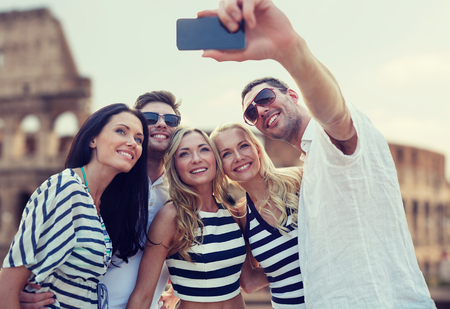 summer, europe, tourism, technology and people concept - group of smiling friends taking selfie with smartphone over coliseum background