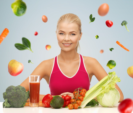 health care decisions: people, healthy eating, vegetarian and health care concept - happy woman with organic food and falling vegetables over gray background