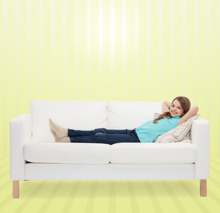 chilling: home, leisure, people and happiness concept - smiling little girl lying on sofa over yellow striped background Stock Photo