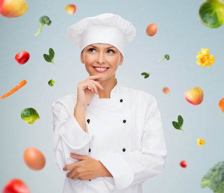 cooking and food concept - smiling female chef, cook or baker dreaming over falling vegetables on gray background