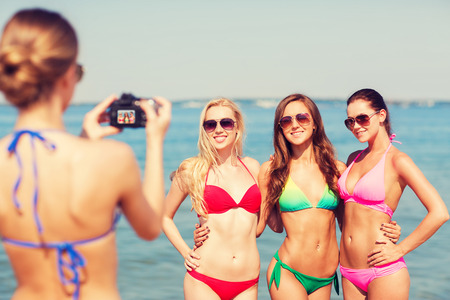 group picture: summer vacation, gesture, travel and people concept - group of smiling young women photographing by camera and waving hands on beach