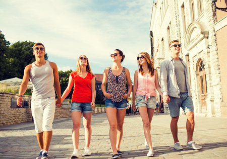 people travelling: friendship, leisure, summer, gesturer and people concept - group of smiling friends walking and holding hands in city