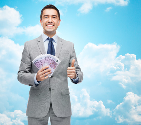 business money: business, people and finances concept - smiling businessman with european money showing thumbs up over blue sky with clouds background