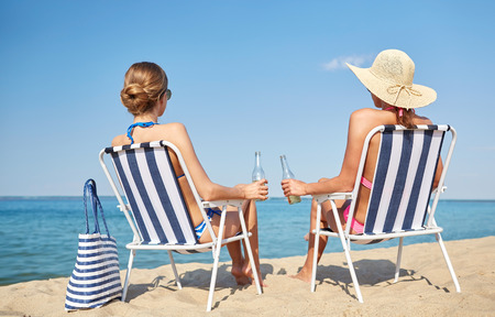 beach chairs: summer vacation, travel and people concept - happy women drinking beer and sunbathing in lounges on beach