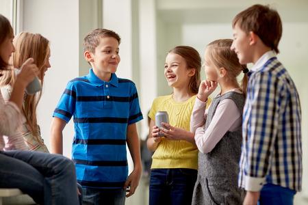 gente comunicandose: educación, escuela primaria, las bebidas, los niños y las personas concepto - grupo de niños de la escuela con las latas de refrescos hablando en el pasillo Foto de archivo