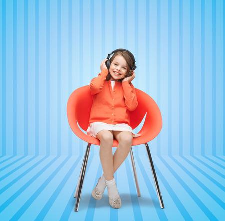 niños sentados: gente, ocio, afición y el concepto de entretenimiento - niña feliz escuchando música en los auriculares sobre fondo azul de rayas Foto de archivo