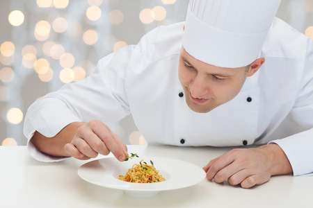 professional chef: cooking, profession, haute cuisine, food and people concept - happy male chef cook decorating dish over christmas holidays lights background Stock Photo