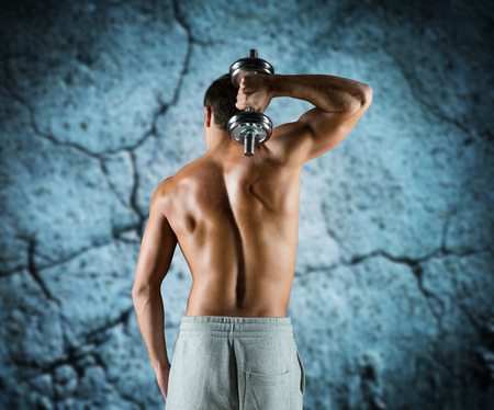 back to work: sport, fitness, weightlifting, bodybuilding and people concept - young man with dumbbell flexing biceps over concrete wall background from back