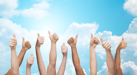 up: gesture, people, human race and international society concept - human hands showing thumbs up over blue sky and white clouds background