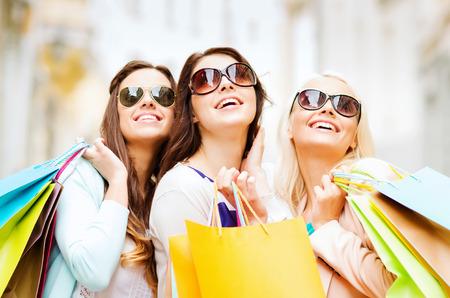 Compras y concepto de turismo - hermosas chicas con bolsas de la compra en ctiy Foto de archivo - 41730586