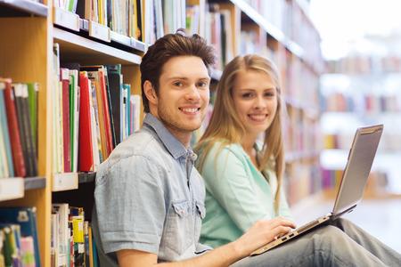 образование: люди, образование, технологии и школы понятие - счастливые студенты с ноутбуком компьютерных сетей в библиотеке Фото со стока