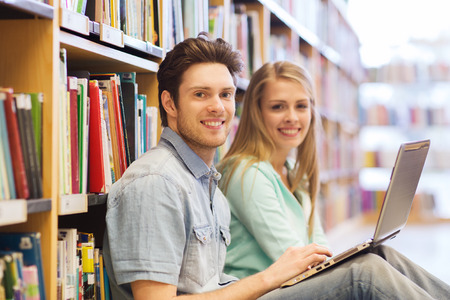 Persone, l'istruzione, la tecnologia e il concetto di scuola - studenti felice con reti di computer portatile in biblioteca Archivio Fotografico - 41730590