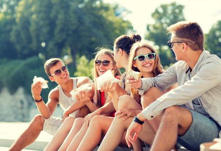 comiendo: amistad, ocio, verano y concepto de la gente - grupo de amigos sonrientes en gafas de sol que se sientan con la comida en la plaza de la ciudad