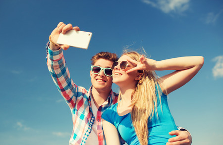 romantic sky: summer, vacation, holidays, technology and friendship concept - smiling couple with smartphone making selfie outdoors Stock Photo