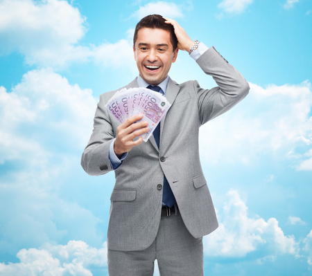 eur: business, people and finances concept - happy laughing businessman with euro money over blue sky with clouds background