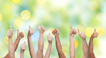 gesto, la gente, la raza humana y el concepto de sociedad internacional - manos humanas que muestran los pulgares para arriba más luces de fondo verde