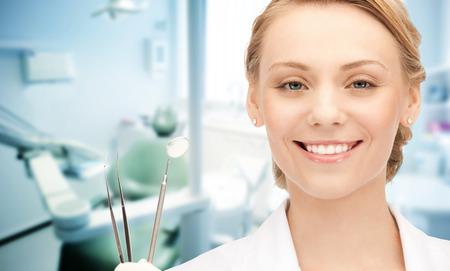 人、医学、口腔病学・医療コンセプト - 医療事務の背景の上のツールで幸せな若い女性歯科医