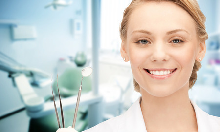 supplies: people, medicine, stomatology and healthcare concept - happy young female dentist with tools over medical office background