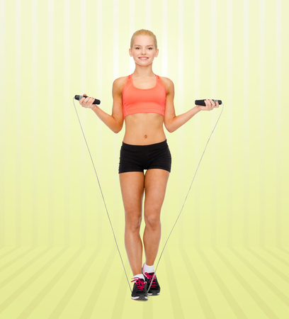 woman rope: sport, fitness, people and weight loss - smiling sporty woman jumping  with skipping rope over yellow striped background