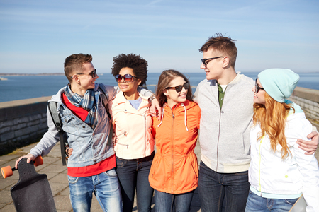beautiful boys: tourism, travel, people, leisure and teenage concept - group of happy friends in sunglasses hugging and laughing on city street