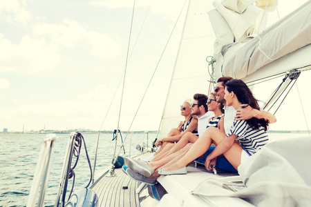 latin couple: vacation, travel, sea, friendship and people concept - smiling friends sitting on yacht deck