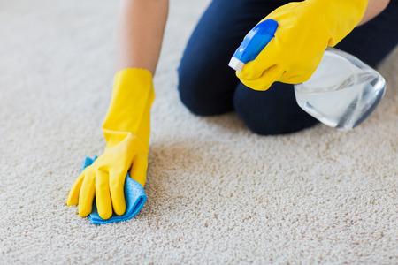 las personas, el trabajo doméstico y de limpieza concepto - cerca de la mujer en los guantes de goma con un paño y detergente aerosol de limpieza de alfombras en casa Foto de archivo