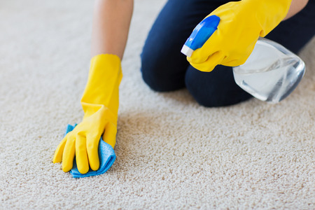sprayer: people, housework and housekeeping concept - close up of woman in rubber gloves with cloth and detergent spray cleaning carpet at home