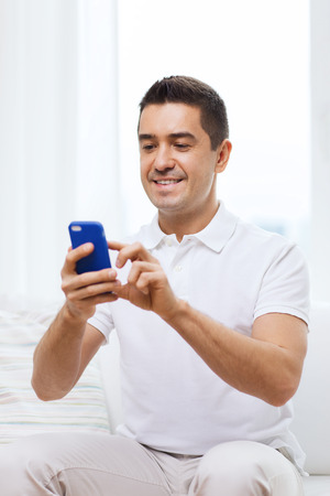 people   lifestyle: technology, people, lifestyle and communication concept - happy man with smartphone at home Stock Photo