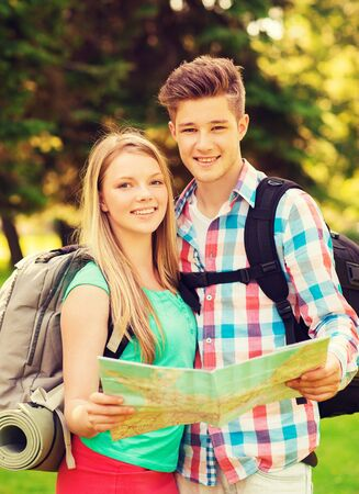 teenage couple: travel, vacation, tourism and friendship concept - smiling couple with map and backpack in forest