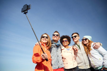 at leisure: tourism, travel, people, leisure and technology concept - group of smiling teenage friends taking selfie with smartphone and monopod outdoors