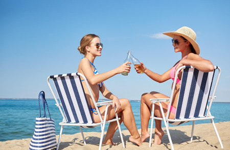 loungers: summer vacation, travel and people concept - happy women drinking beer and sunbathing in lounges on beach