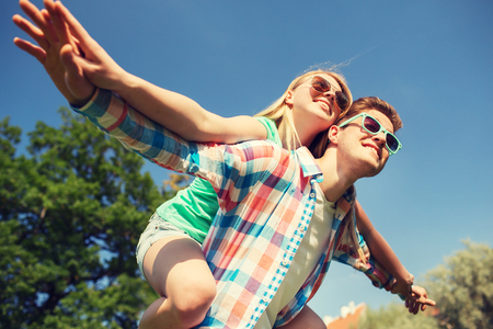 love park: holidays, vacation, love and friendship concept - smiling couple having fun in park Stock Photo