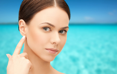 blue sea: people, beauty, hearing and healthcare concept - face of beautiful woman touching her ear over blue sea and sky background Stock Photo