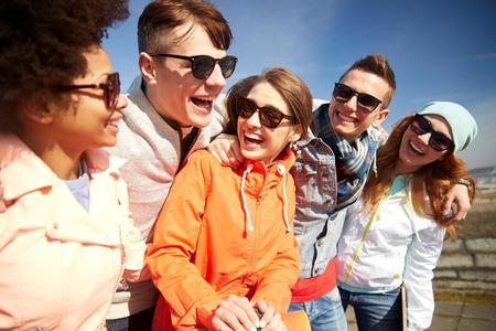 pareja de adolescentes: turismo, viaje, gente, ocio y concepto de adolescente - grupo de amigos felices en gafas de sol que abrazan y ríen en calle de la ciudad