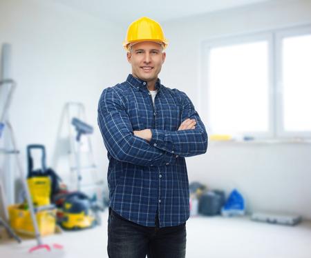 constructor: reparación, construcción, edificio, personas y concepto de mantenimiento - sonrientes constructor masculino o trabajador manual en el casco sobre la habitación con el fondo de los equipos de trabajo Foto de archivo