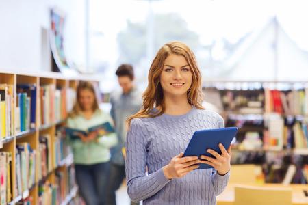 Menschen, Bildung, Technologie und Schule Konzept - Studenten glücklich Mädchen oder eine Frau mit Tablette-PC-Computer in der Bibliothek