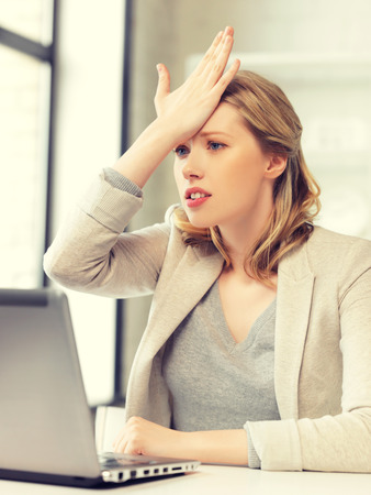 miserable: picture of stressed woman with laptop computer