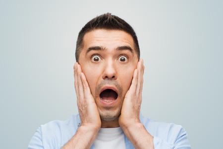 Angst, Emotionen, Horror und Menschen Konzept - Angst Mann Geschrei und berührte sein Gesicht auf grauem Hintergrund