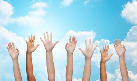 gente saludando: gesto, saludo, la caridad y las partes del cuerpo concepto - la gente agitando las manos sobre el cielo azul y nubes blancas de fondo Foto de archivo