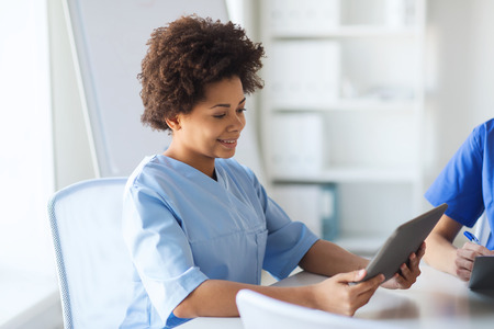 health professionals: medicine, people and healthcare concept - happy female doctor or nurse with tablet pc computer at hospital