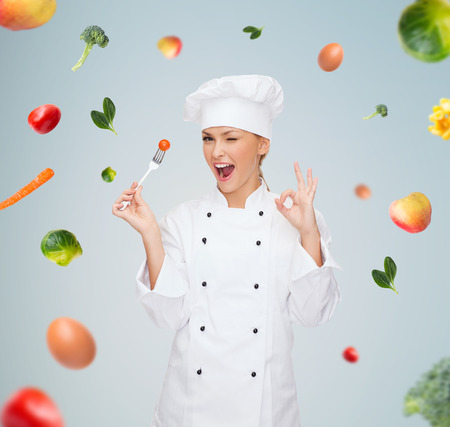 ok: cooking and food concept - smiling female chef, cook or baker with fork and tomato showing ok sign over falling vegetables on gray background Stock Photo