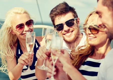 vasos de agua: vacaciones, viaje, mar, la amistad y la gente concepto - amigos sonrientes con copas de champán en el yate Foto de archivo