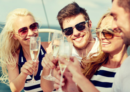 seaside: vacation, travel, sea, friendship and people concept - smiling friends with glasses of champagne on yacht