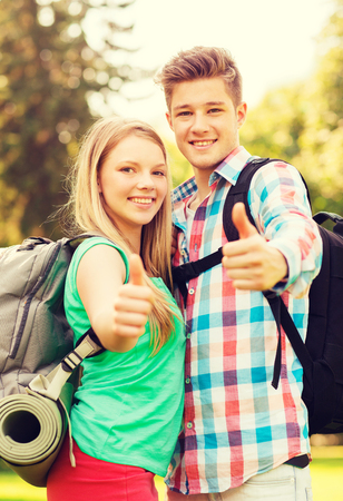 mat like: travel, vacation, tourism, gesture and friendship concept - smiling couple with backpacks showing thumbs up in nature