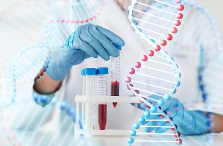 biologia: la ciencia, la química, la biología, la medicina y la gente concepto - cerca de la mujer de ciencias tubo joven que sostiene con la muestra de sangre en el laboratorio clínico y estructura de la molécula de adn