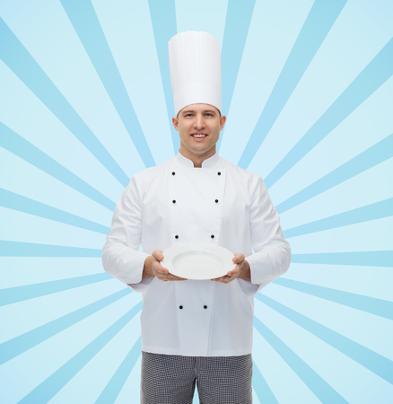 empty of people: cooking, profession, advertisement and people concept - happy male chef cook showing something on empty plate over blue burst rays background