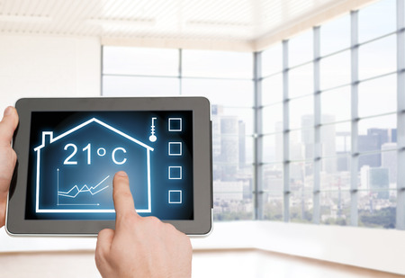 temperature: home, housing, people and technology concept - close up of man hands pointing finger to tablet pc computer and regulating room temperature over empty flat background